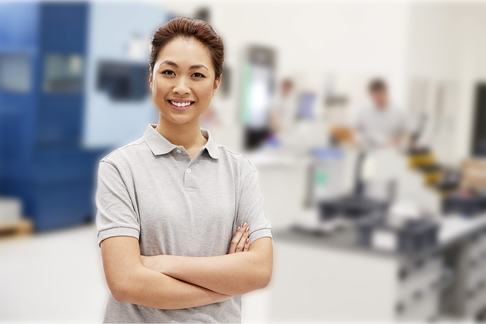 Woman smiling with blurred factory floor in background